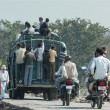 India Orchha - 21 February 2011 - Overloaded public transport bus carrying people on top and hanging out at the back. — Stok fotoğraf #30509745