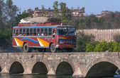 India Orchha - 21 February 2011 - Public transport bus traverses bridge over Betwa River with Raja Palace in background. — Stock Photo