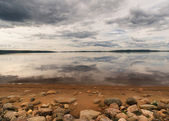 Rocky beach fronts lake reflecting dramatic skies in Finnish Lap — Stock Photo