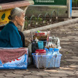 Old woman street vendor selling water while sitting on her haunc — Stock Photo