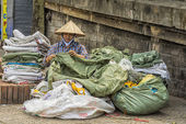 Woman repairs old plastic bags in the street of Hanoi. — Stock Photo