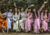 Seven joyful female university seniors dressed in Ao Dai. — Stock Photo