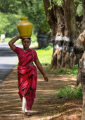 Indian woman carries pot of water on her head. — Stock Photo