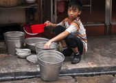 Boy doing the dishes on the sidewalk. — Stock Photo