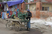 Man with sugar cane pressing machine mounted on a cart. — Stock Photo