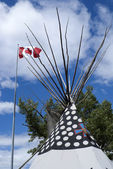 Canadian flag over top of teepee. — Stock Photo
