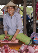 Young female butchers sits in the middle of fresh cut pieces of  — Stockfoto