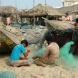 Two fishermen busy mending nets in Puri, Orissa, India. — Stock Photo