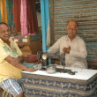 Men at a table with an old sewing machine, Delhi - Stock Photo