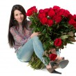 Brunette woman holding a large bouquet of red roses — Stock Photo #23961405