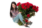 Brunette woman holding a large bouquet of red roses — Stock Photo