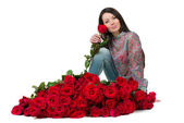 Brunette woman with a big bouquet of red roses — Stock fotografie