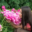 Young woman smelling a flower peony — Stock Photo