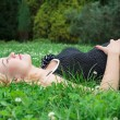 Stock Photo: Pregnant womlying on grass