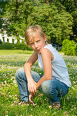 Boy sitting on grass — Stock Photo