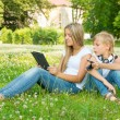 Boy and girl sitting in the park and enjoy the tablet — Stock Photo