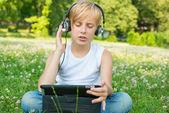 Menino com o tablet e fones de ouvido — Foto Stock