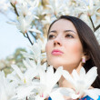 Woman in the flowers of magnolia — Stock Photo