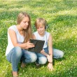 Boy and girl sitting in the park and enjoy a digital tablet — Stock Photo