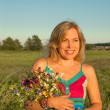 Woman with wild flowers smiling — Stock Photo