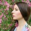 Portrait of a woman near a flowering tree — Stock Photo