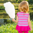 Foto Stock: Girl stands near river and keeps cotton candy