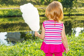 Girl stands near the river and keeps the cotton candy — Stock Photo