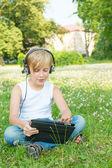デジタル タブレットで公園に座っている少年 — ストック写真