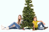 Boy and girl sitting under the tree — Stock Photo