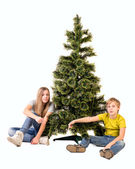 Boy and girl sitting under the tree and point the finger — Stock Photo