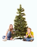 Boy and girl sitting under the Christmas Tree — Stock Photo