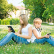 Boy and girl sitting in park with digital tablet — Stock Photo