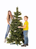 Boy and girl standing near the Christmas tree — Stock Photo