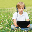 Boy sits in park with digital tablet — ストック写真 #36110523