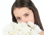Woman looks out because of a bouquet of white chrysanthemums — Stock Photo