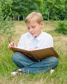 Schoolboy sitting in the park and writing in a notebook — Stockfoto