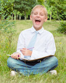 Écolier assis dans le parc avec un ordinateur portable et de rires — Photo