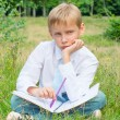 Schoolboy sitting in the park with a notebook upset — Stock Photo