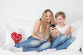 Teenagers sitting on the couch with the phone and laughing — Foto Stock