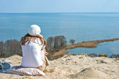 Woman in a beret sits on a mountain and looking at the sea — Stock Photo