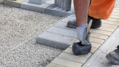 Worker laying brick pavement to gravel at construction site — Stockvideo