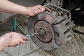Car mechanic work on disc brakes — Stok fotoğraf