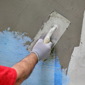 Wall insulation, spreading mortar over mesh — Stock Photo