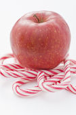 Red apple on top of Candy Canes — Stock Photo