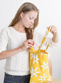 Young confident woman with reusable shopping bag — Stok fotoğraf