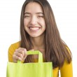 Attractive young woman holding green shopping bag — Stock Photo