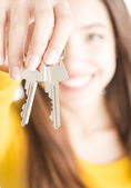Attractive young woman holding keys — Stock Photo