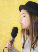 Attractive young woman singing with microphone — Stock Photo