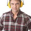 Serious handyman with earmuffs on white background - Stock Photo