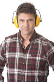 Serious handyman with earmuffs on white background — Stock Photo